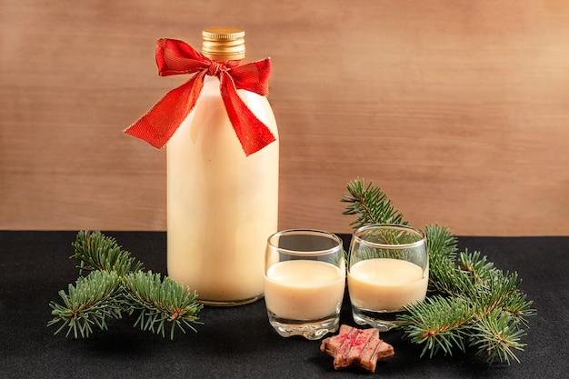 Zabaione fatto in casa in bottiglia e due bicchieri con decorazioni di natale su fondo in legno Foto Premium