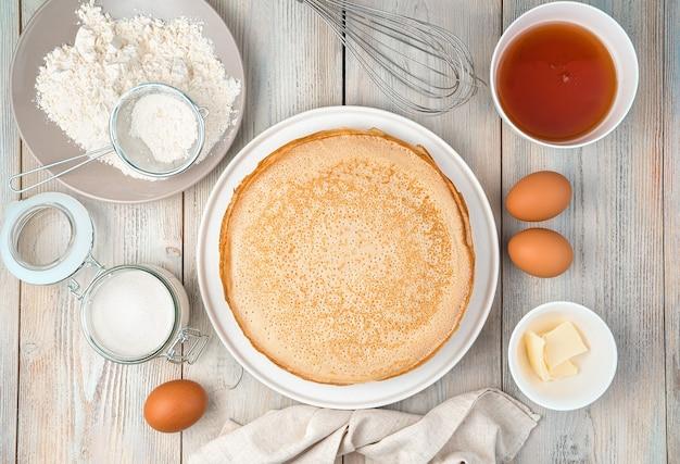 Frittelle fatte in casa, fritte su un piatto e ingredienti per cucinarle su una superficie leggera. vista dall'alto, con spazio per scrivere. il concetto di cucina, ricette, mardi gras. Foto Premium