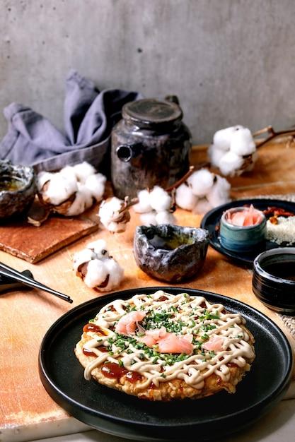 Frittella di cavolo okonomiyaki giapponese fast food fatta in casa con cipolla, zenzero sottaceto, salsa mayo su piastra in ceramica nera. lay piatto Foto Premium
