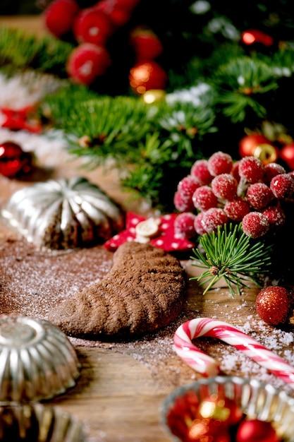 Fatti in casa tradizionali biscotti di pasta frolla di natale mezzelune al cioccolato con zucchero a velo di cacao in piatto di ceramica con stampi per biscotti, abete, decorazioni di stelle di natale rosse su fondo in legno Foto Premium