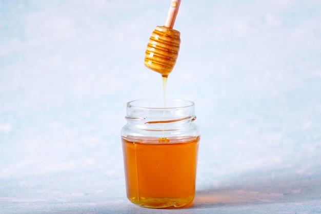 Mestolo di miele e miele profumato che cadono in una ciotola Foto Premium