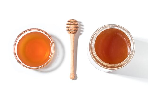 Mestolo di miele e miele in vaso sulla superficie bianca. Foto Premium