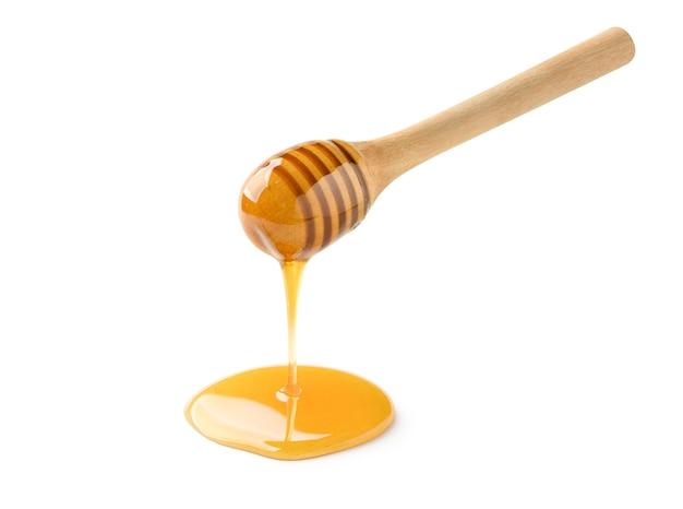 Miele che gocciola dal mestolo di miele isolato su bianco Foto Premium