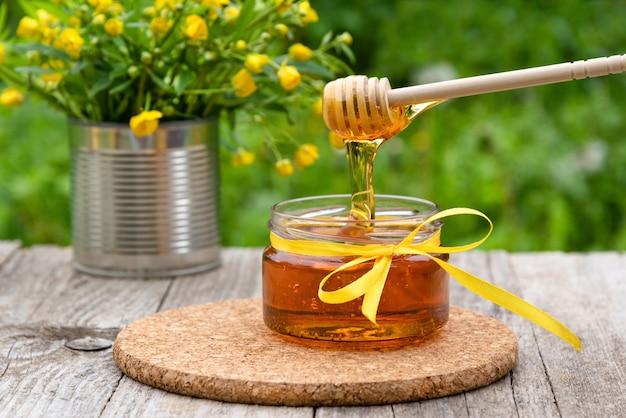 Il miele gocciola dal cucchiaio nel barattolo Foto Premium