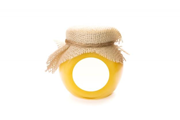 Il barattolo di vetro del miele con l'etichetta in bianco deride su isolato. Foto Premium