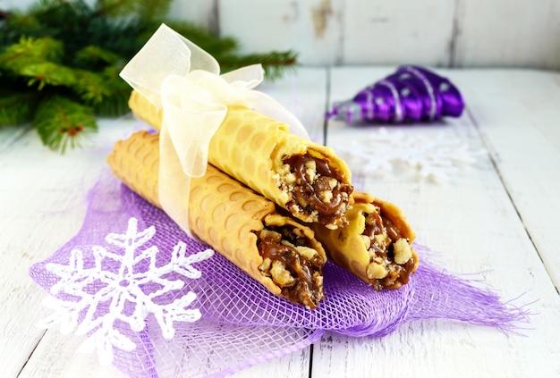 Cialde fatte in casa al miele sotto forma di tubi con ripieno di noci caramellate su sfondo chiaro. avvicinamento Foto Premium