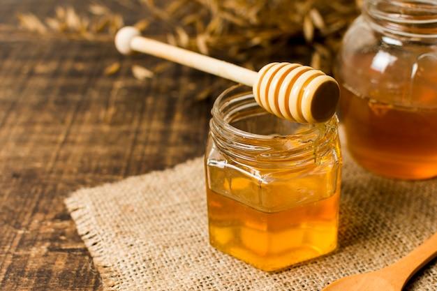 Cucchiaio di miele sul barattolo Foto Premium
