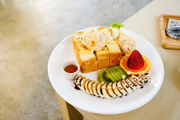 Pane tostato al miele servito con frutta mista, banana a fette, gelato e guarnito con fetta di mandorle e sciroppo di miele Foto Premium