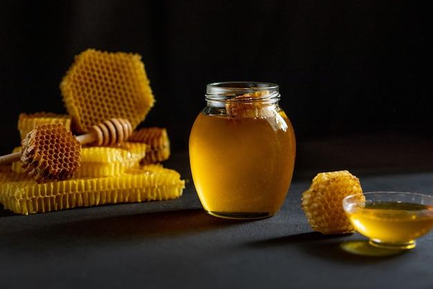 Miele con favo sulla tavola nera Foto Premium