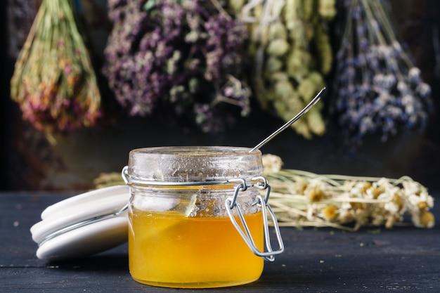 Miele con tè sul tavolo rustico backgound con erbe Foto Premium