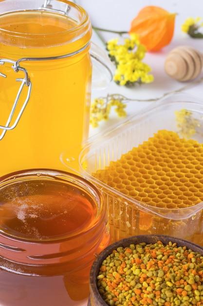 Favo, polline e vasetti di miele. mestolo miele e fiori Foto Premium
