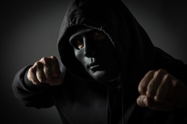 Uomo incappucciato irriconoscibile con i pugni chiusi Foto Premium