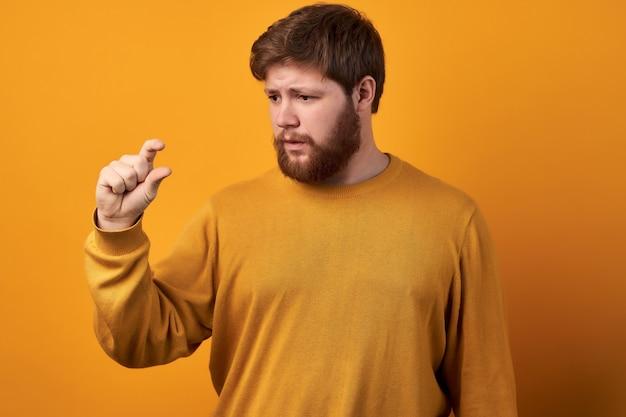 Il colpo orizzontale del maschio barbuto stupito mostra qualcosa di molto piccolo, indossa una camicia di jeans casual, isolato su sfondo bianco Foto Premium