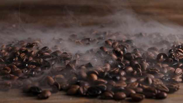 Chicchi di caffè caldi sul tavolo di legno Foto Premium