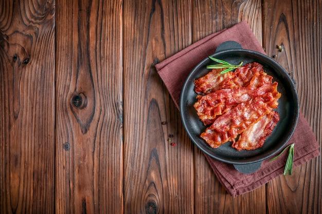 Fette di pancetta croccante fritte calde e rametti di rosmarino in padella su legno Foto Premium