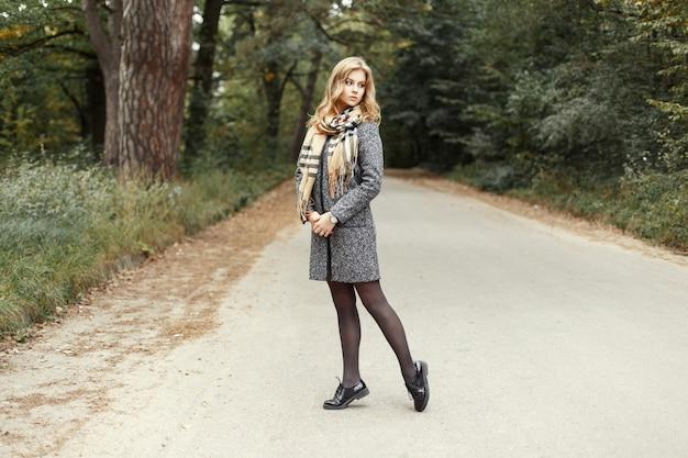 Modello caldo donna in sciarpa calda vintage in un cappotto e scarpe che camminano sulla strada nel parco. Foto Premium