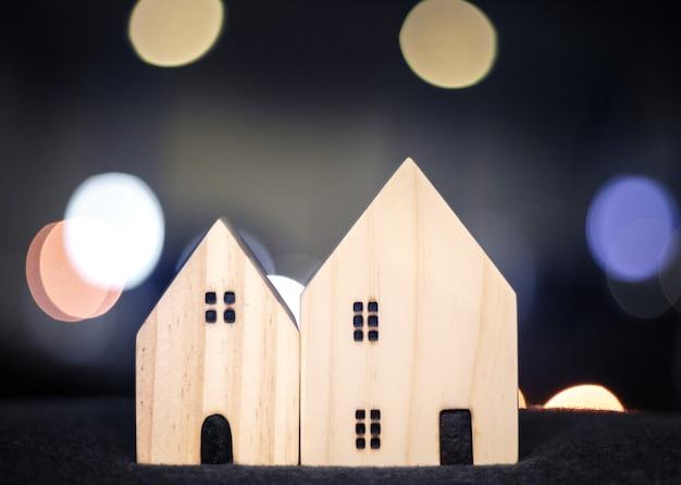 Modello di legno della casa o della casa per il concetto felice della famiglia con la luce del bokeh dalla città moderna del centro Foto Premium