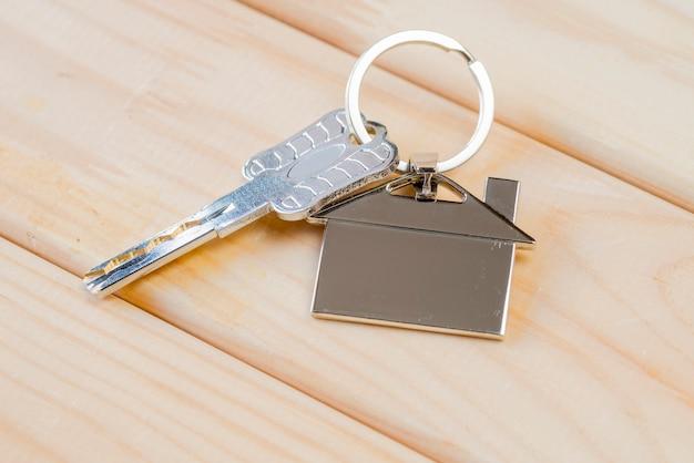 Chiave di casa con portachiavi casa sul tavolo di legno Foto Premium