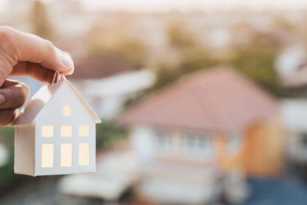 Modello di casa nella mano dell'agente del broker di assicurazione casa o nella persona del venditore. Foto Premium