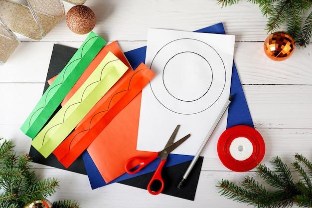 Come realizzare ghirlande natalizie dalla carta. istruzioni passo passo. progetto di decorazione per le vacanze di capodanno fai da te fatto a mano. passo 1 Foto Premium