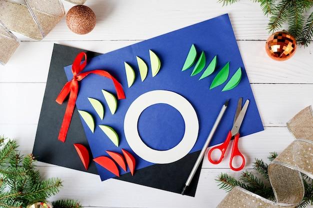 Come realizzare ghirlande natalizie dalla carta. istruzioni passo passo. progetto di decorazione per le vacanze di capodanno fai da te fatto a mano. passo 2 Foto Premium