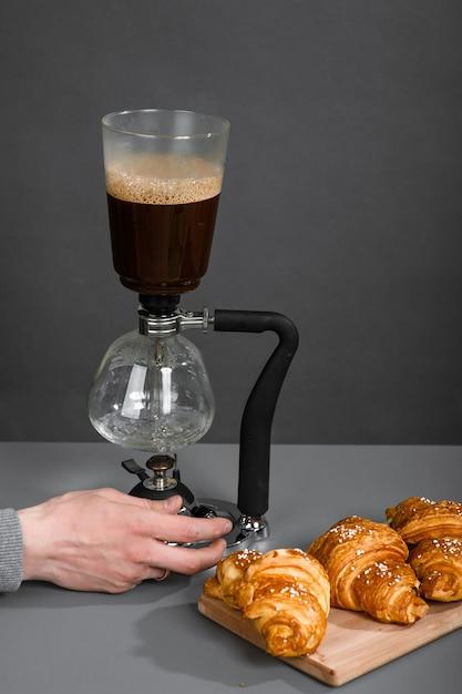 La mano umana regola la caffettiera per preparare il caffè a goccia in una stanza con pareti grigie. Foto Premium