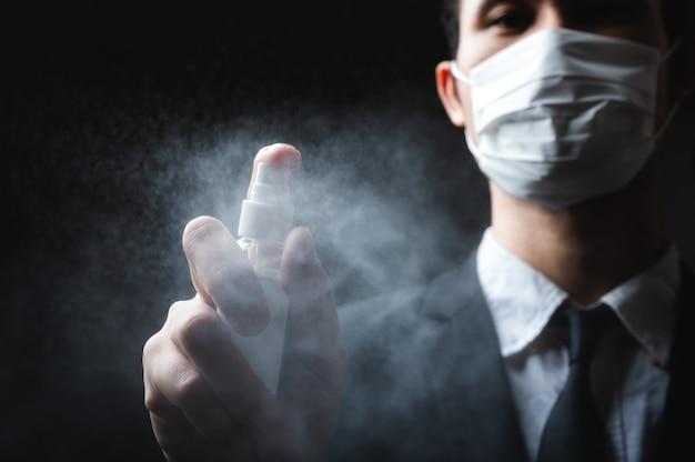 Mano umana e flacone spray antisettico su sfondo scuro. controllare le misure di prevenzione epidemica del coronavirus. Foto Premium