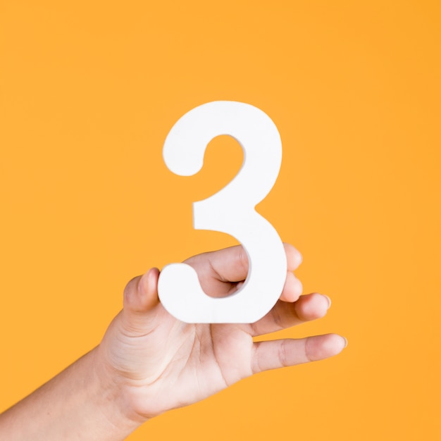 Mano umana che regge il numero 3 su uno sfondo giallo Foto Premium