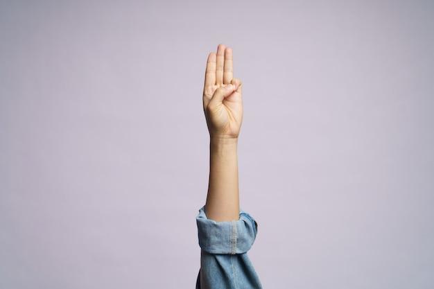 Mano umana che mostra tre dita isolate. Foto Premium