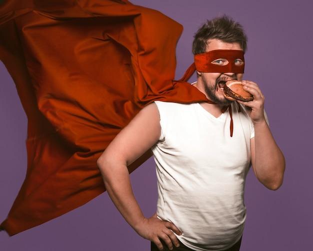 L'uomo affamato del supereroe mangia il grande hamburger con carne. l'uomo in mantello rosso volante mangia guardando la telecamera su sfondo viola uva. concetto di snack fast food Foto Premium