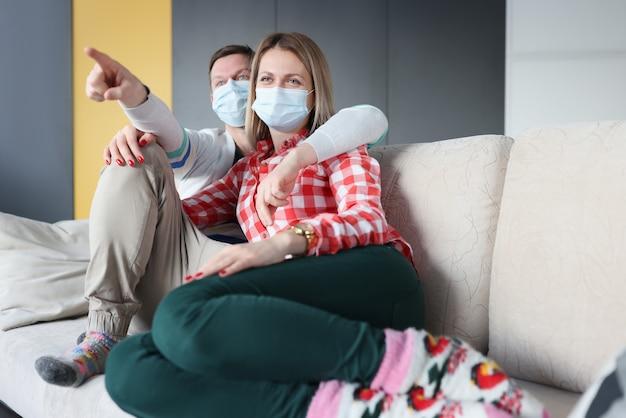 Ubicazione del marito e della moglie sul divano con maschere mediche protettive. autoisolamento durante il covid-19 Foto Premium