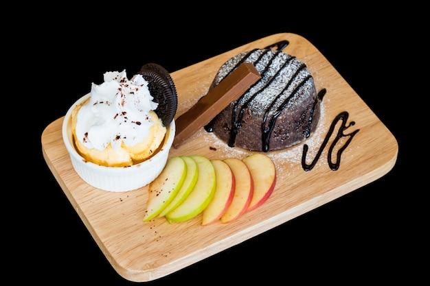 Gelato. brownies del cioccolato di homade con il gelato di vanila in piatto di legno su backgr nero Foto Premium