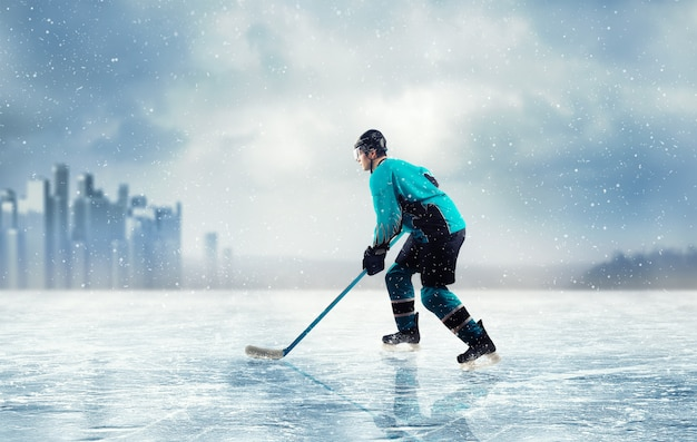 Giocatore di hockey su ghiaccio in azione sul lago ghiacciato Foto Premium