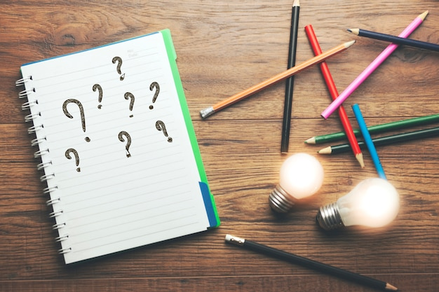 Idea con il punto interrogativo sul taccuino con le matite Foto Premium