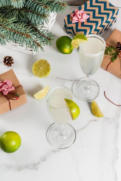Idee per bevande di natale e capodanno. cocktail margarita champagne, guarniti con lime e sale. sul tavolo bianco con decorazioni natalizie, copia spazio Foto Premium