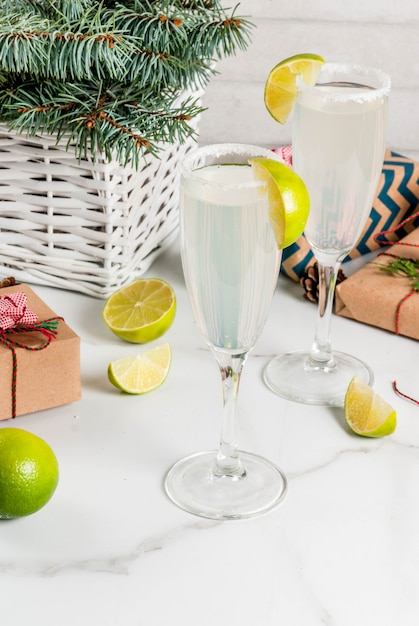Idee per bevande di natale e capodanno. cocktail margarita champagne, guarniti con lime e sale. sul tavolo bianco con decorazioni natalizie, copyspace Foto Premium