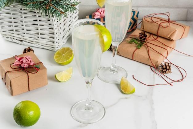 Idee per bevande di natale e capodanno. cocktail margarita champagne, guarniti con lime e sale Foto Premium