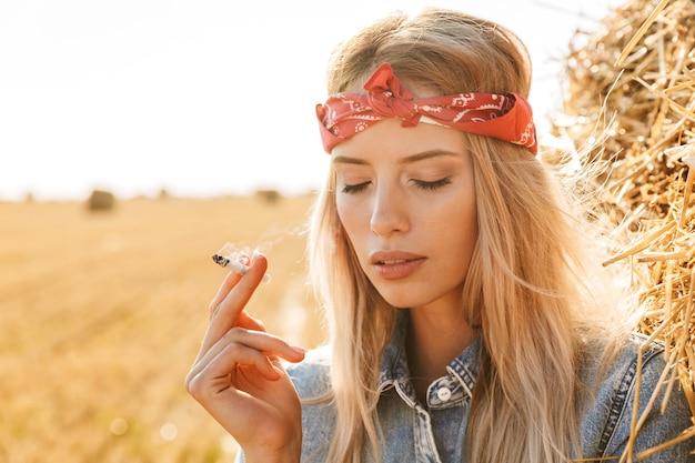 Immagine di bella donna 20s in piedi vicino a un grande pagliaio in campo dorato e fumo di sigaretta durante la giornata di sole Foto Premium