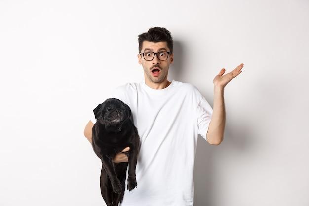 Immagine di uomo hipster confuso con cane e scrollare le spalle, non so, alzando la mano perplesso, in piedi con il suo animale sopra bianco. Foto Premium