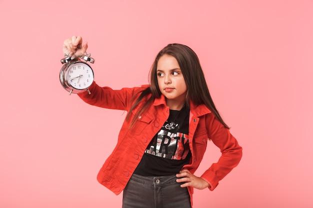 Immagine della ragazza insoddisfatta 8-9y in sveglia casuale della holding mentre levandosi in piedi, isolata sopra la parete rossa Foto Premium
