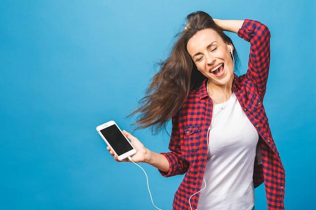 Immagine di felice giovane donna ascoltando musica in cuffia Foto Premium