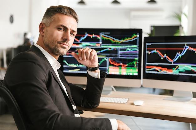 Immagine dell'uomo d'affari moderno 30s che indossa tuta lavorando in ufficio sul computer con grafici e grafici a schermo Foto Premium