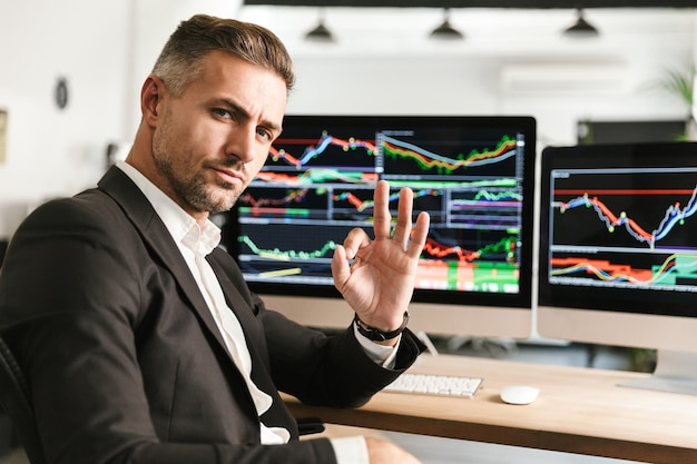 Immagine di uomo d'affari unshaved 30s indossa tuta lavorando in ufficio sul computer con grafici e grafici a schermo Foto Premium