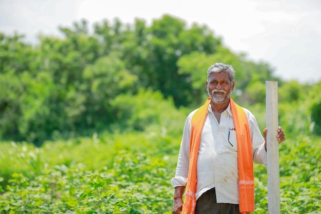 Contadino indiano tenendo il tubo al campo di cotone. Foto Premium