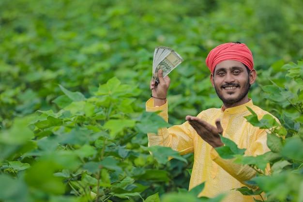 Coltivatore indiano che mostra soldi al campo di cotone Foto Premium