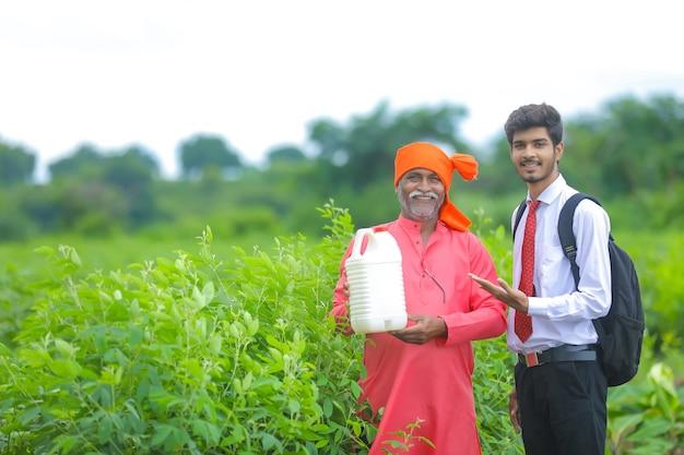 Contadino indiano con agronomo al campo, agricoltore e agronomo che mostra botle di fertilizzante Foto Premium