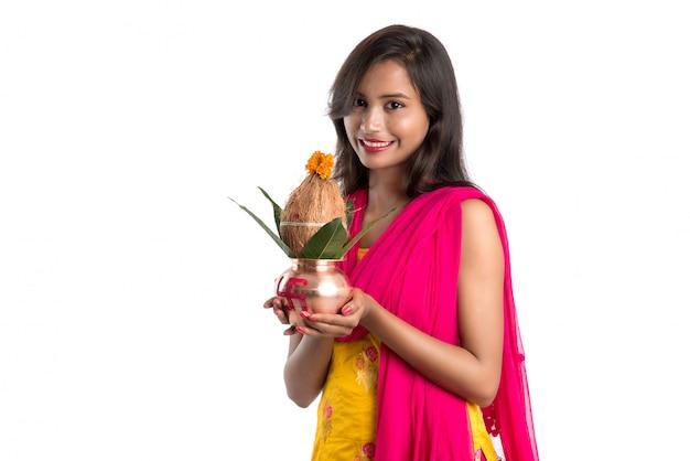 Ragazza indiana con in mano un tradizionale kalash in rame, festival indiano, kalash in rame con cocco e foglie di mango con decorazioni floreali, essenziali nella pooja indù. Foto Premium