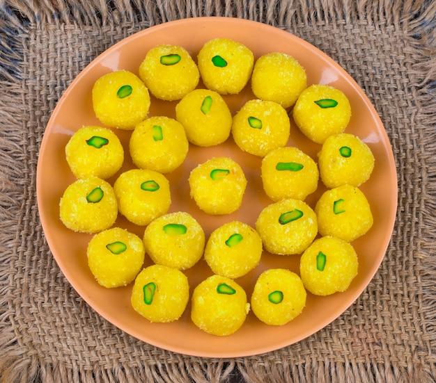 Laddu indiano della noce di cocco dell'alimento dolce su fondo di legno Foto Premium