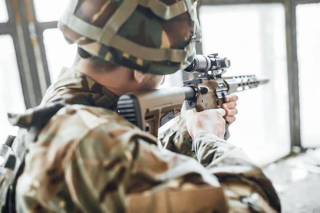 Soldato di fanteria che spara durante l'addestramento al combattimento militare. guerra, esercito, arma Foto Premium