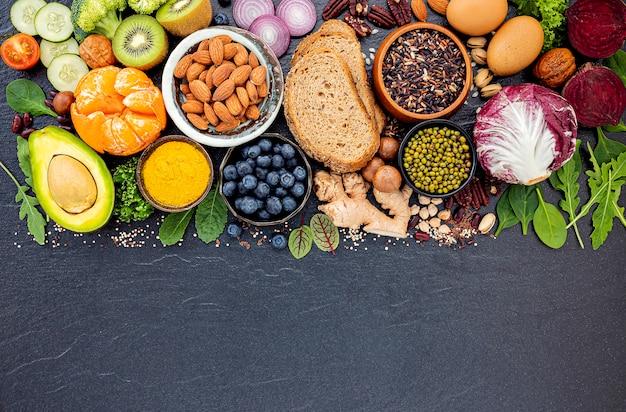 Ingredienti per la selezione di alimenti sani istituito su sfondo di pietra scura. Foto Premium